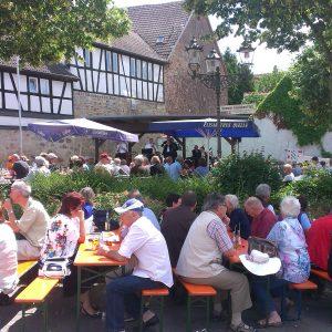 Gut besuchter Dorfplatz bei einem früheren Jazz Konzert an einem sommerlichen Vormittag, dazu passend