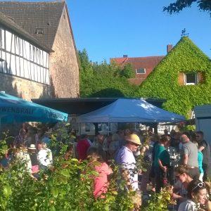 Dichtes Gedränge auf dem Dorfplatz während des Wochenmarkts.