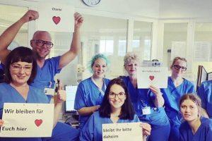 Pflegekräfte der Charité in Berlin in blauen Kitteln mit Postern