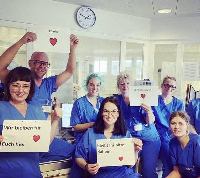 """Pflegekräfte der Charité in Berlin in blauen Kitteln mit Postern """"bleibt ihr bitte daheim"""" , """"wie bleinen für Euch hier"""" und """"wir halten durch"""""""